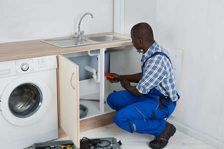 Young African Male Plumber Fixing Sink With Worktool In Kitchen Stock Photo