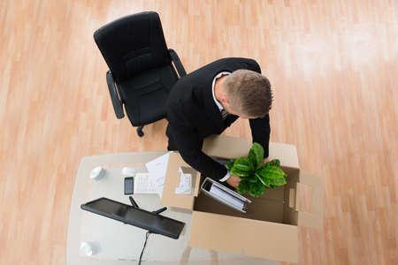 transferred: Businessman Packing Belongings In Cardboard Box At The Desk