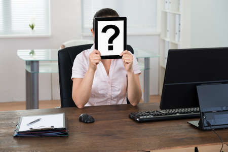 search query: Young Businesswoman With Question Mark Sign Sitting At Desk