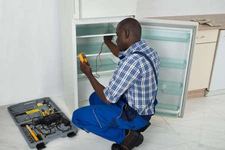 refrigerator kitchen: Happy African Technician Repairing Refrigerator Appliance In Kitchen Room