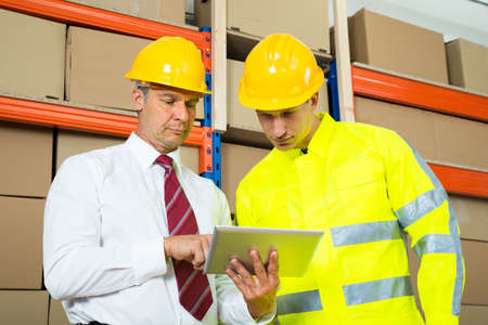 warehouse: Warehouse Worker And Manager Looking At Laptop In A Large Warehouse Stock Photo