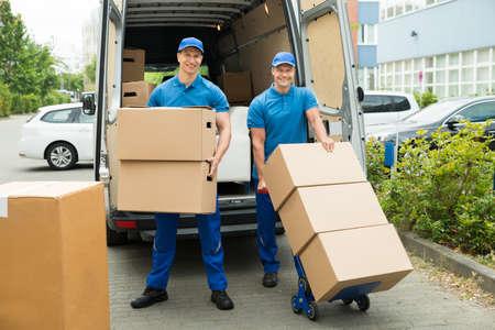 Twee Gelukkige mannelijke werknemers Laden Stapel van kartonnen dozen in de truck