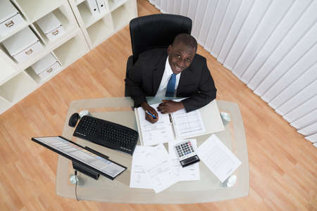 black businessman: High Angle View Of African Businessman Calculating Bills In Office