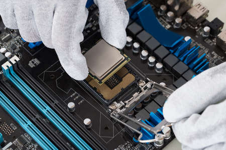 working at computer: Close-up Of Person Hands Installing Central Processor In Motherboard Stock Photo
