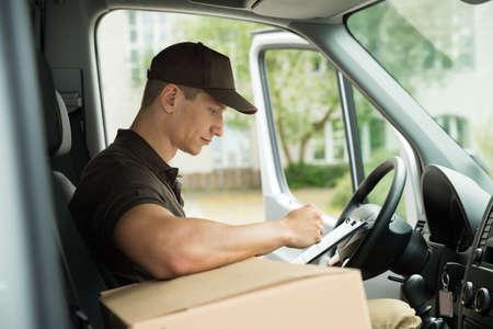 Junge Delivery Man Überprüfen Liste in Zwischenablage In Van Standard-Bild