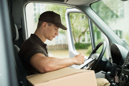 stock car: Young Delivery Man Checking List On Clipboard In Van