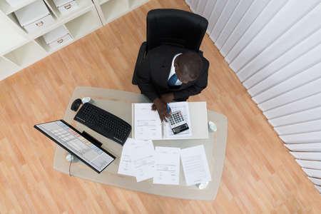 auditoría: Vista elevada del hombre de negocios de África Cálculo de Cuentas en la oficina Foto de archivo