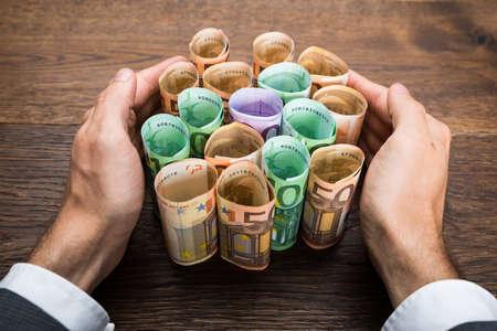 billets euros: Close-up de la main de un homme d'affaires Protéger Euro Billets