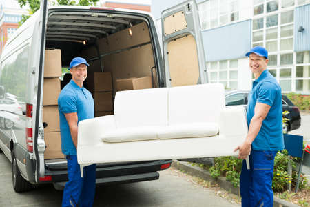 relocating: Two Happy Male Workers Putting Furniture And Boxes In Truck
