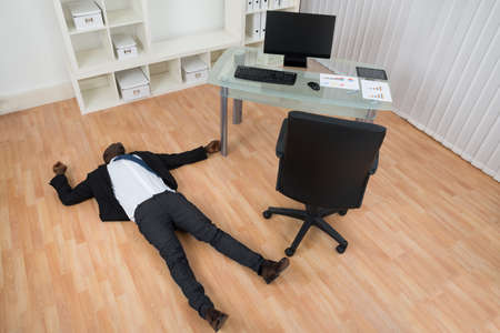 fallen: Unconscious Young African Businessman Lying On Floor In Office Stock Photo