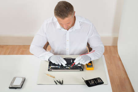 computer equipment: Young Man Examining Laptop Motherboard With Multimeter At Desk