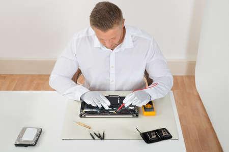 laptop repair: Young Man Examining Laptop Motherboard With Multimeter At Desk