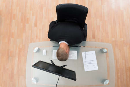 top down: Young Businessman Leaning On Computer Keyboard At Desk