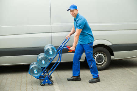 water bottles: Young Happy Delivery Man Holding Trolley With Water Bottles Stock Photo