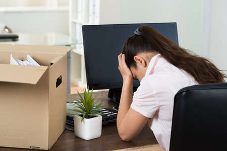 transferred: Dismiss Young Businesswoman With Belongings Sitting At Desk In Office