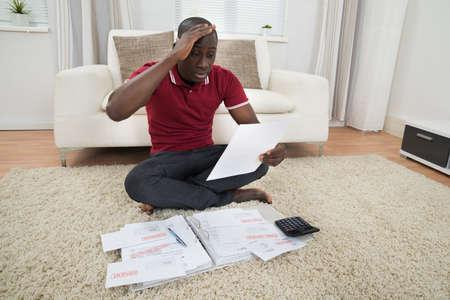 confundido: Retrato de joven preocupante africano sentado sobre una alfombra que mira el documento Foto de archivo