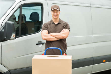 moving van: Young Happy Delivery Man With Cardboard Boxes On Trolley In Front Of Van