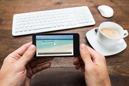 filizanka kawy: Zamknij się osoby oglądania wideo na telefonie z filiżanką herbaty przy biurku Zdjęcie Seryjne
