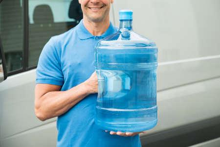 Primer De Entrega hombre en uniforme azul que lleva la botella de agua grande Foto de archivo - 42196994