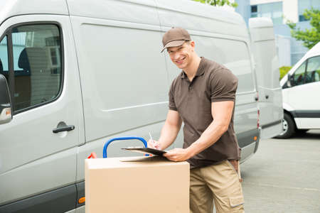 one young man: Young Happy Delivery Man With Cardboard Boxes Writing On Clipboard Stock Photo