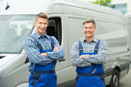 overall: Two Happy Repairmen In Overall With Arms Crossed In Front Of Van Stock Photo