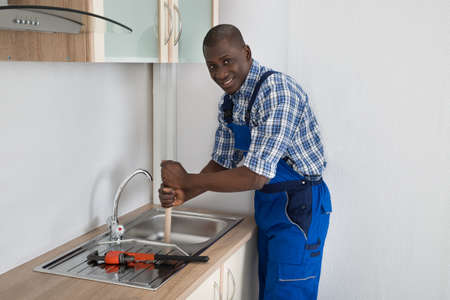 Young Happy African Plumber Using Plunger To Unclog Kitchen Sink