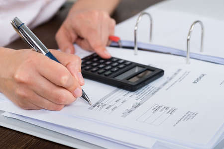 Close-up Of Accountant Doing Calculation With Calculator In Office Standard-Bild