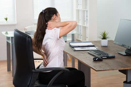 chory: Młoda businesswoman siedzi na krześle mając Backpain W Urzędzie Zdjęcie Seryjne