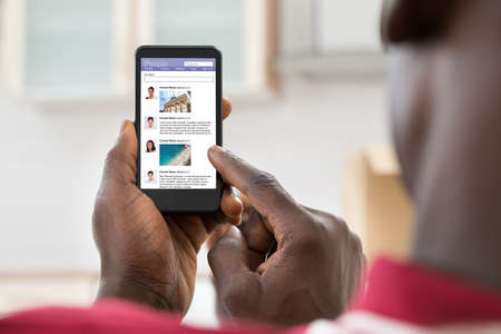 web browsing: Close-up Of African Young Man Surfing On Social Networking Site Using Cellphone