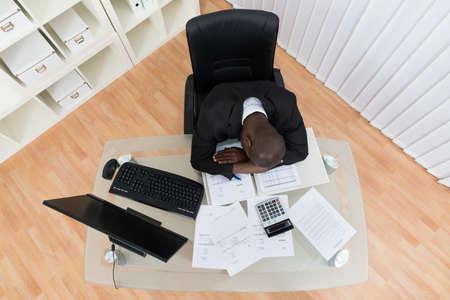 personas sentadas: Vista elevada del hombre de negocios tensionado que duerme en el escritorio