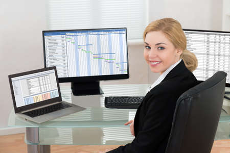 computers office: Happy Businesswoman On Office Chair Working At Computers