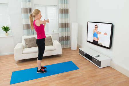 Young Woman Exercising In Front Of Television In Living Room photo