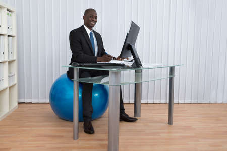 pilates ball: Portrait Of Happy African Businessman Working Sitting On Pilates Ball Stock Photo