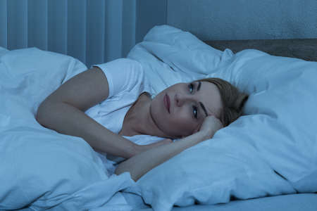 Young Woman Suffering From Insomnia Lying In Her Bed