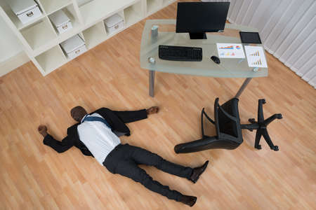 unconscious: Unconscious Young African Businessman Lying On Floor In Office Stock Photo