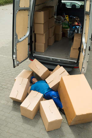 whacked: Unconscious Male Worker Lying On Street Surrounded With Boxes Stock Photo
