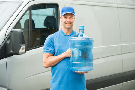 delivery: Happy Delivery Man Holding Water Bottle In Front Of Truck