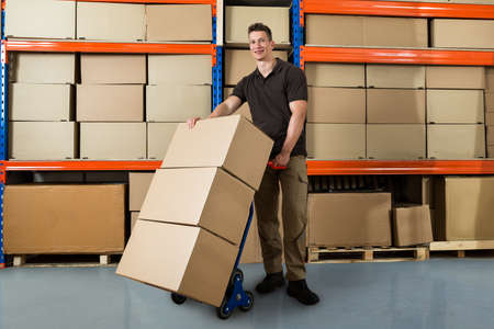 Happy Male Worker With Boxes On Hand Truck In Large Warehouse