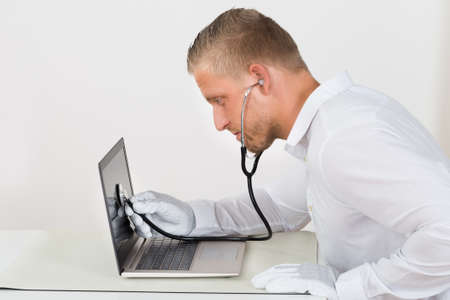 hardware repair: Male Technician With Stethoscope And Laptop At Desk