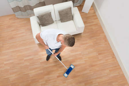 domesticity: High Angle View Of Young Man Mopping Floor At Home