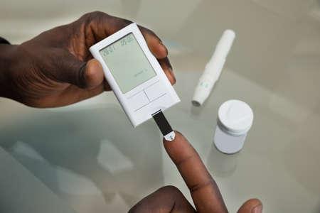 Close-up van de patiënt Handen Meten Glucose Level Bloedonderzoek Met Glucometer Stockfoto