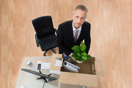 transferred: Young Businessman Packing Personal Things In Box