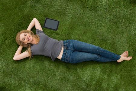 in jeans: Mujer joven que miente con la tableta digital En Hierba Verde En Césped