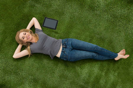 jean: Young Woman Lying With Digital Tablet On Green Grass In Lawn