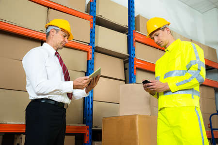 inventory: Warehouse Worker Checking The Inventory With Manager In A Large Warehouse