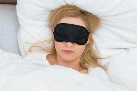 sleep: Mujer joven que duerme con la máscara del sueño en el dormitorio