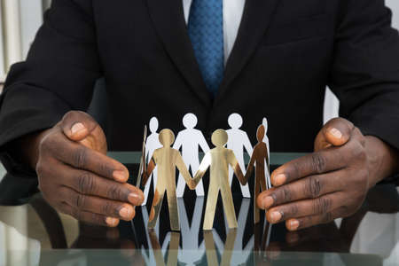 black business man: Close-up Of Businessman Hands Protecting Paper Cutout People At Desk Stock Photo