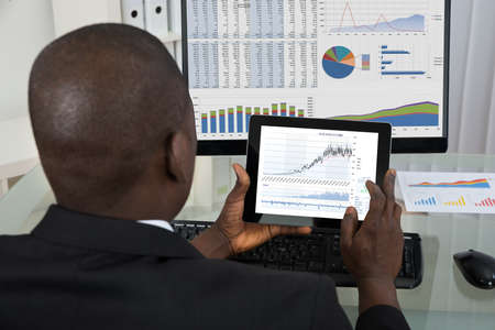 look at: Rear View Of Young African Businessman Analyzing Graph On Digital Tablet In Office