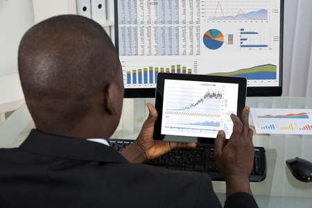 bursatil: Vista posterior del hombre de negocios africano joven Analizar el gráfico en la tableta digital en oficina