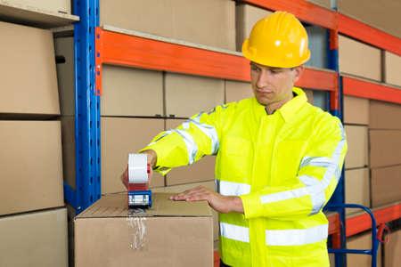 cintas: Trabajador joven de embalaje Caja de cartón con la cinta Arma Dispensador En Almacén
